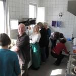 Arbeitsaufteilung in der Küche, fröhliches Grinsen bei allen Beteiligten